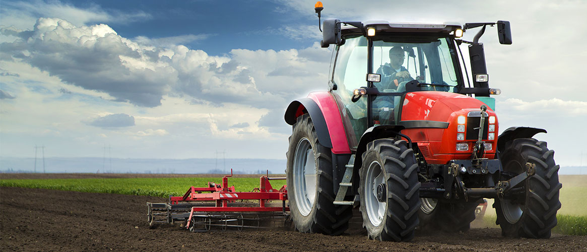 Red tractor with man driving through fields with tiller attachment behind