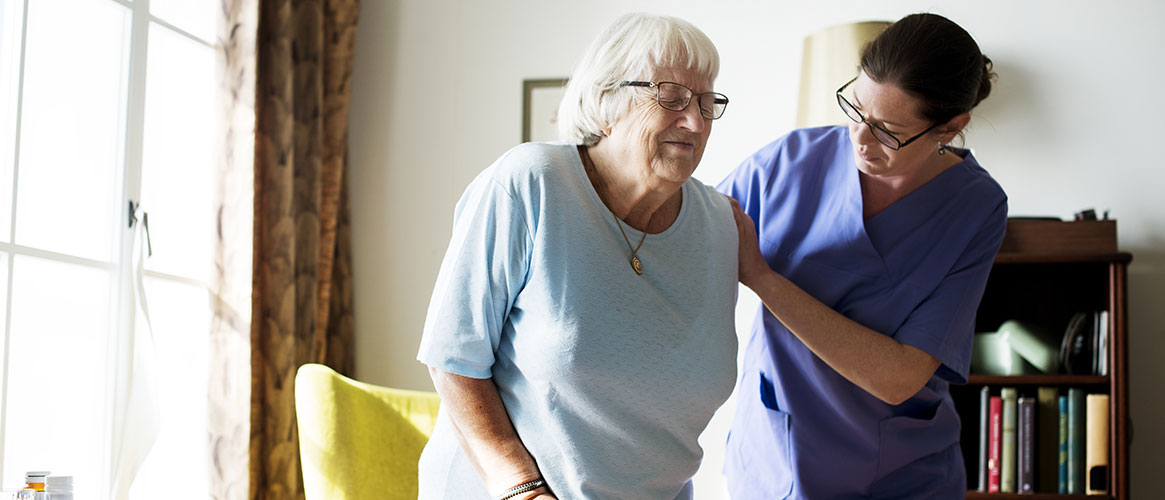 Home health worker helping an elderly resident to stand up
