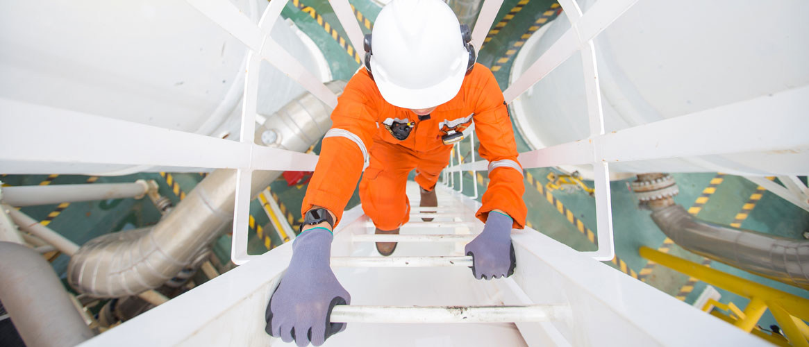 Production operator climbing up ladder to oil and gas process plant