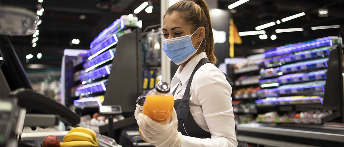 Store clerk wearing mask and gloves in compliance with Cal/OSHA's emergency COVID-19 regulations
