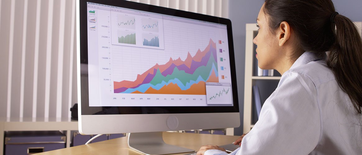 Analyst staring intently at screen full of charts and graphs