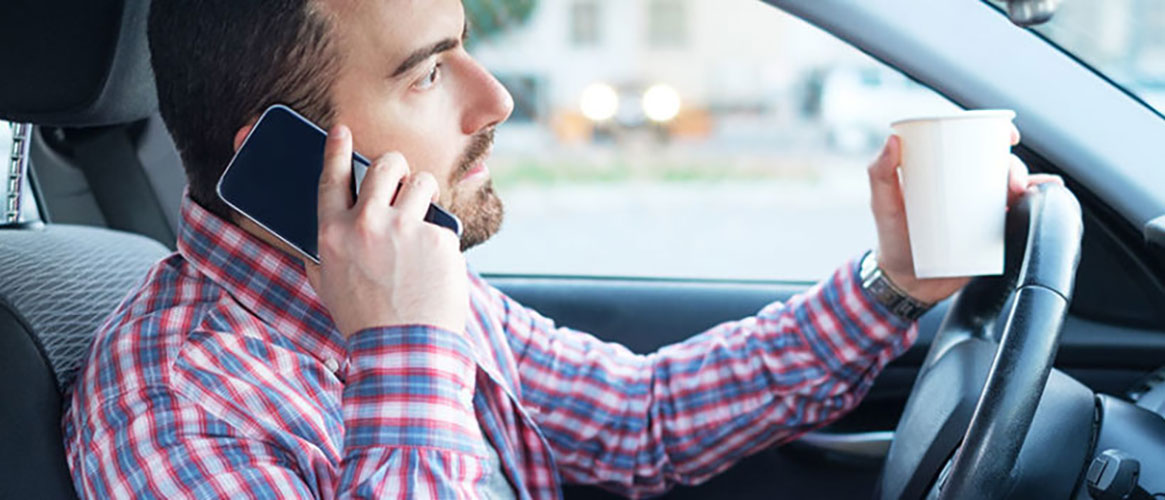 Man driving distracted with mobile phone and coffee