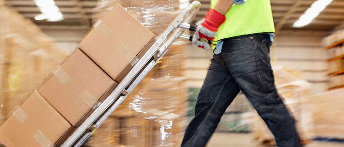 Warehouse worker safely moving heavy boxes with handtruck