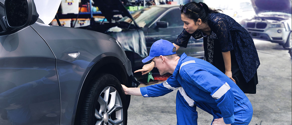 mechanic checking tire wear for customer