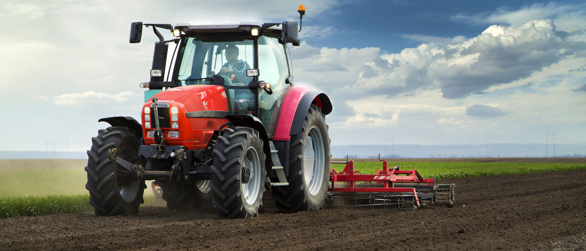 Red tractor safely maneuvering field
