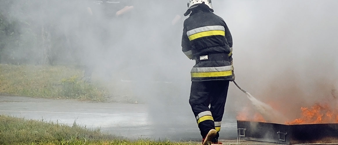 Fire fighter using the PASS method with his fire extinguisher