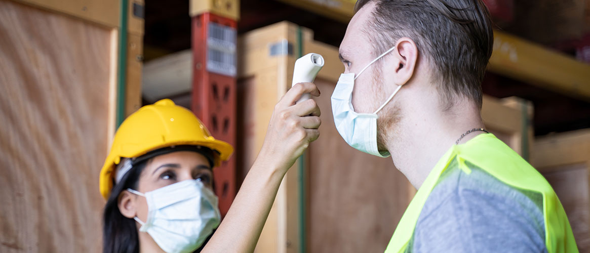Worker's temperature being taken to comply with Cal/OSHA regulations